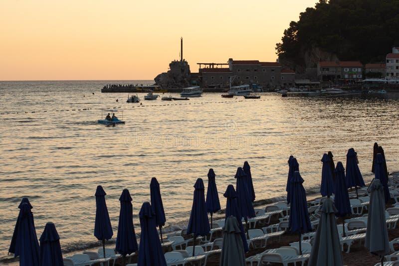 PETROVAC MONTENEGRO - JULI 20, 2018: Sikt från kajen av Petrovac till den gamla slotten och Adriatiskt havet, sommar, solnedgångl royaltyfria bilder