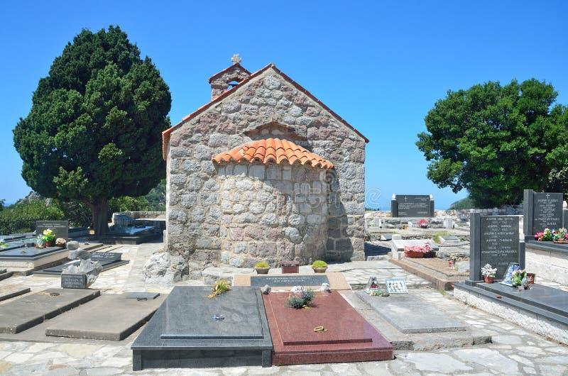Petrovac, Montenegro, Juni, 22, 2015 Die Kirche des Dormition in der Mitte des Kirchhofs im alten Kloster Gradiste, Montag stockfotografie