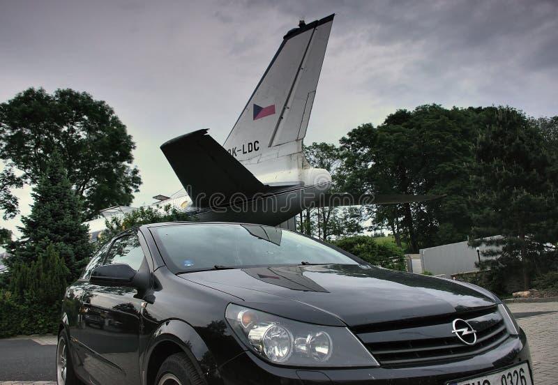 Petrovice Ustecky kraj, Tjeckien - Juni 09, 2019: svart bil Opel Astra framme av trafikflygplantupoleven T-104 som fungerar i dag arkivfoto