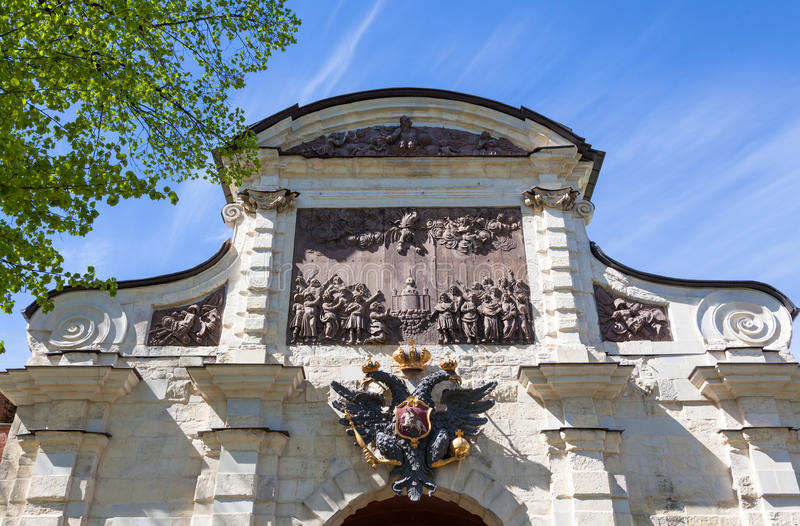 Petrovsky Gates. The State Emblem of Russia and Bas-relief `The overthrow of Simon the Magi by the Apostle Peter` over the Petrovsky Gates of the Peter and Paul royalty free stock photos