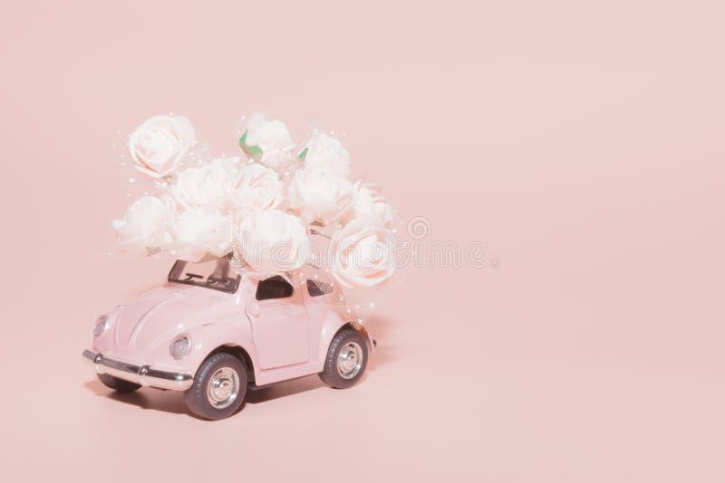 Petrozavodsk, R?ssia - 4 de abril de 2019: Carro retro cor-de-rosa do brinquedo com o ramalhete das rosas brancas no fundo cor-de foto de stock royalty free