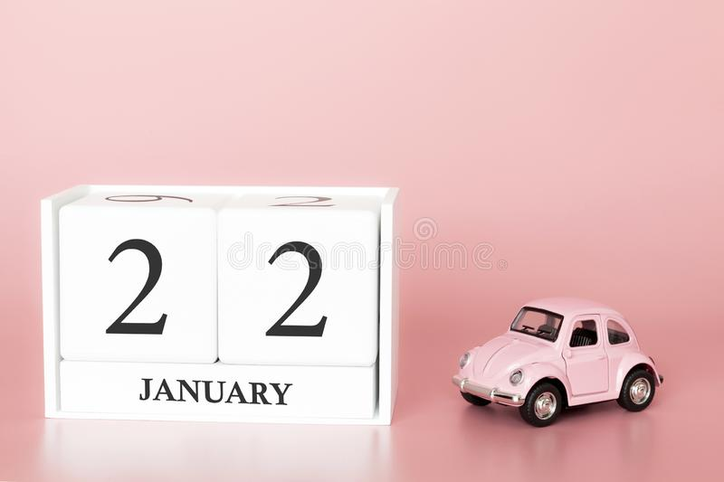 Petrozavodsk, Russia - April 06, 2019: Close-up wooden cube 22nd of January. Day 22 of january month, calendar on a pink. Background with retro car. Winter time stock images