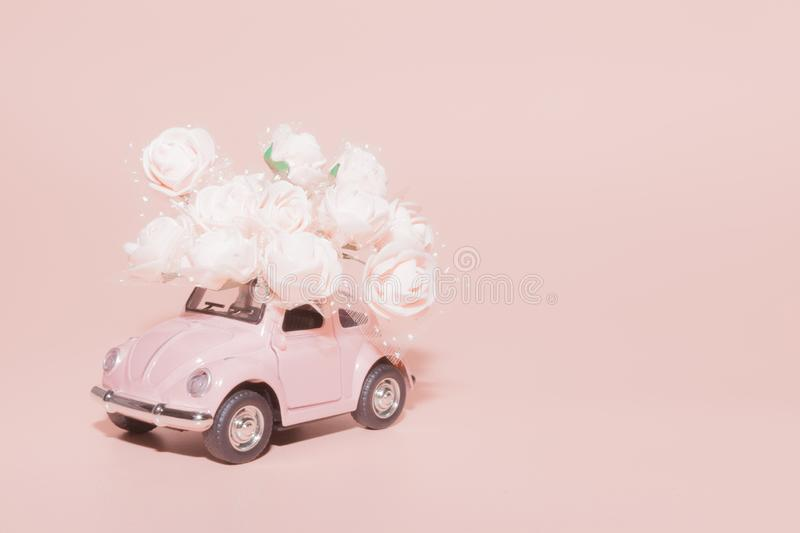 Petrozavodsk, Russia - April 04, 2019: Pink retro toy car with bouquet of white Roses on pink background. Concept Valentine`s day royalty free stock photo