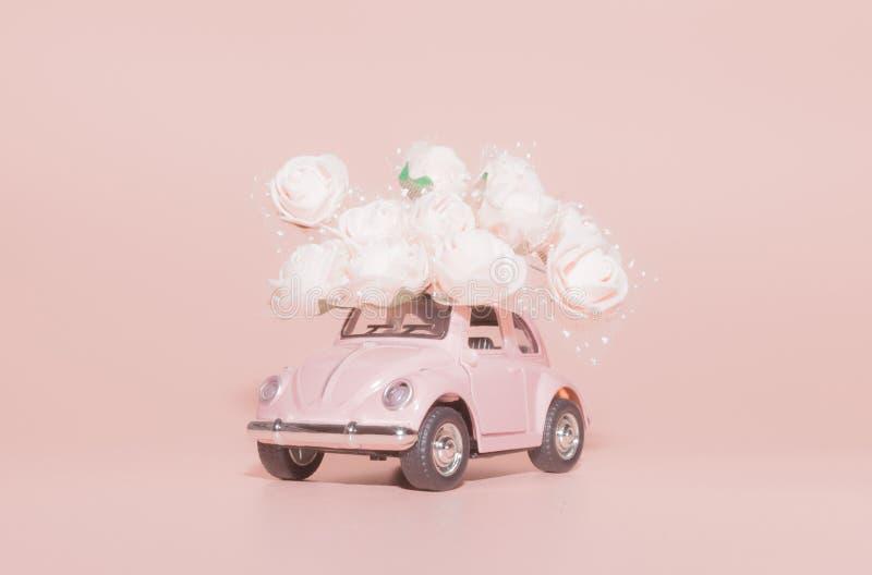 Petrozavodsk, Russia - 4 aprile 2019: Retro automobile rosa del giocattolo con il mazzo delle rose bianche su fondo rosa giorno d fotografia stock