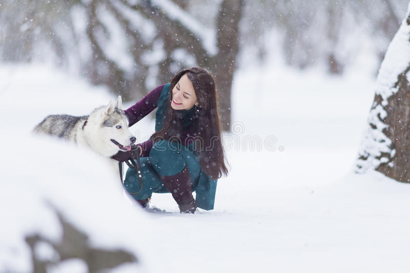 Pets Concepts and Ideas. Happy and Smiling Caucasian Brunette Woman Playing with Husky Dog royalty free stock photography