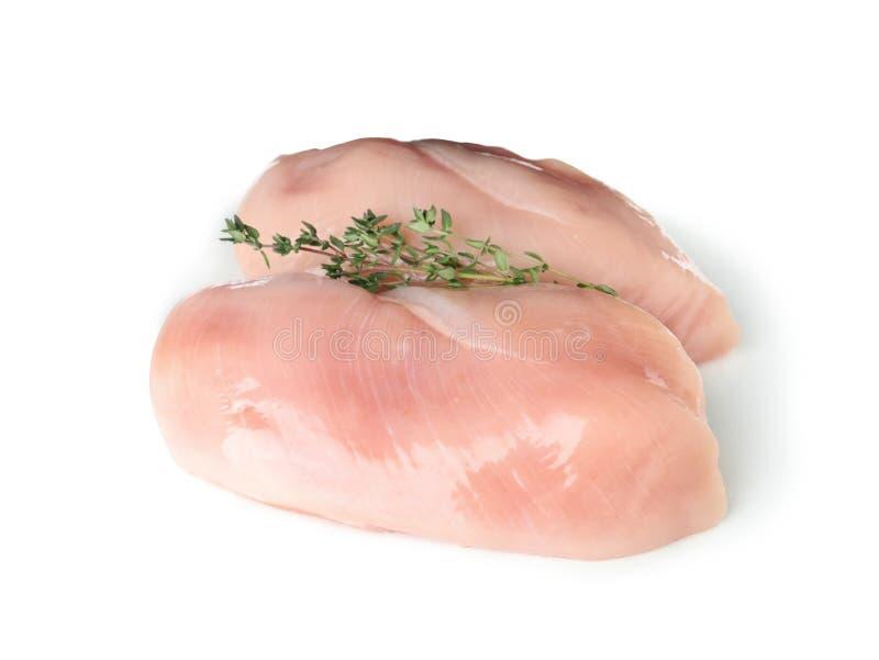 Petti di pollo crudi con timo su bianco Carne fresca fotografia stock libera da diritti