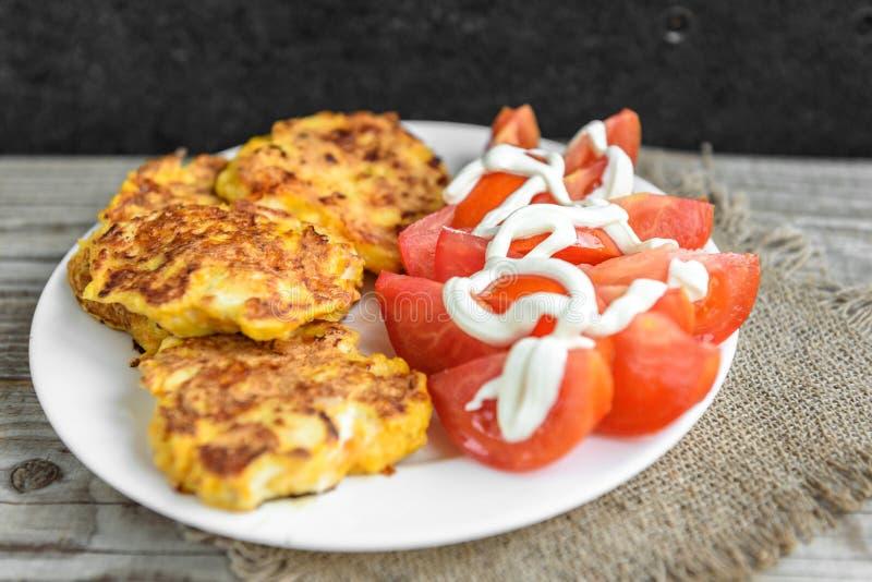 Petti di pollo ricoperti di formaggio, pomodori sul piatto bianco, sulla vecchia tavola di legno fotografia stock
