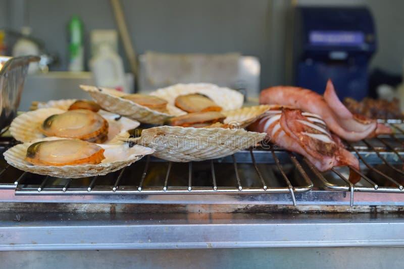Pettini arrostiti e calamari su un girarrosto nel festival della birra, Giappone fotografia stock libera da diritti