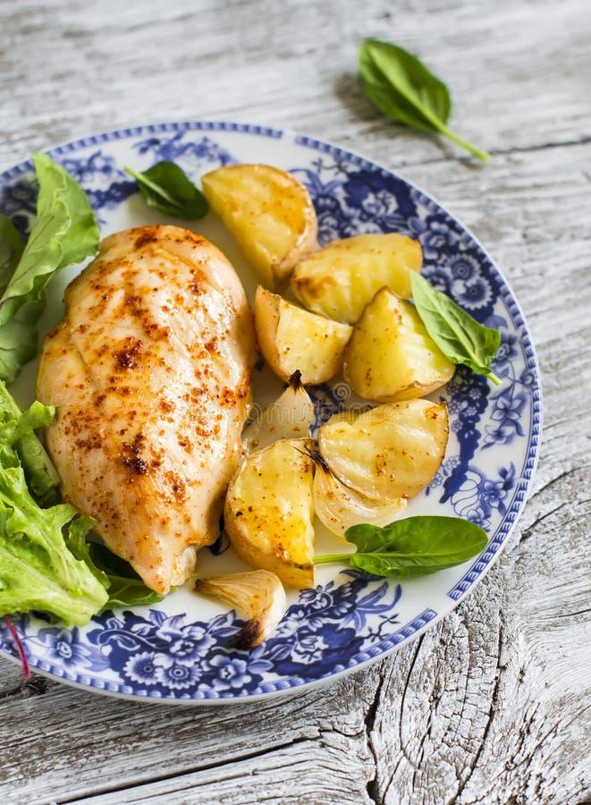 Petto di pollo al forno con le patate e le cipolle su un piatto d'annata fotografie stock