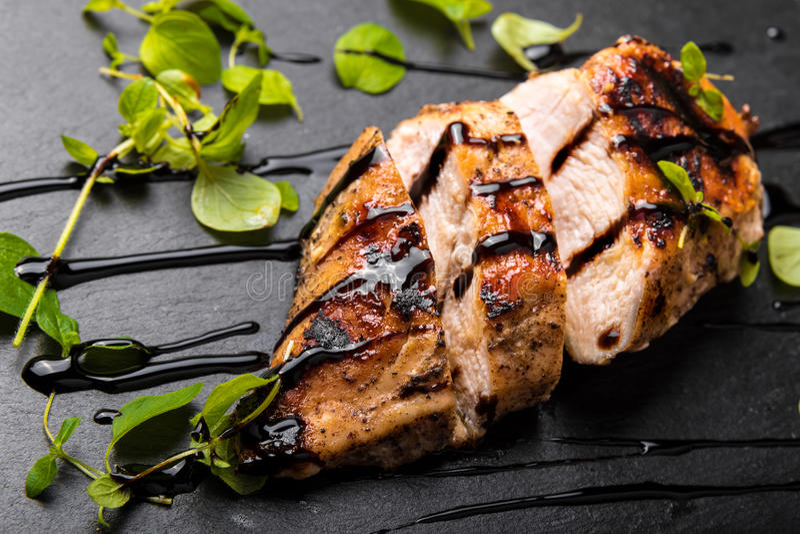 Petto di pollo arrostito su un piatto di pietra nero con aceto balsamico ed origano fotografie stock libere da diritti