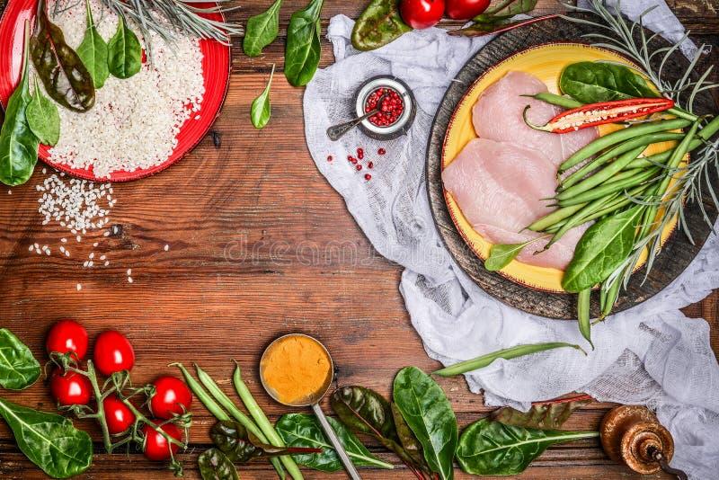 Petto di pollo crudo con riso e gli ingredienti organici freschi delle verdure per la cottura sana sul fondo di legno rustico, vi immagine stock