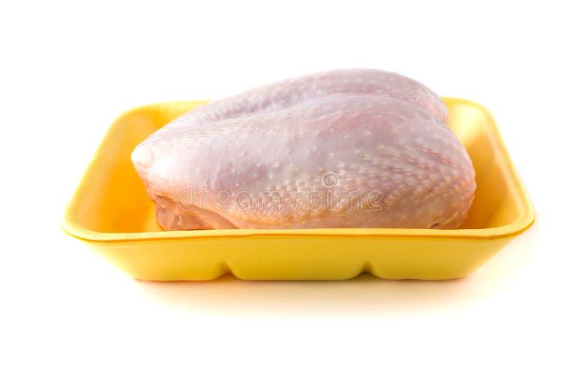 Petto di pollo crudo in un vassoio su un fondo bianco immagine stock