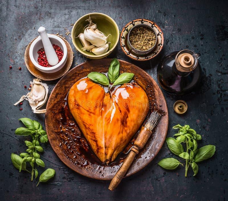 Petto di pollo marinato nella forma del cuore con la spazzola dello sfregamento per la cottura o la griglia su fondo scuro rustic fotografie stock libere da diritti
