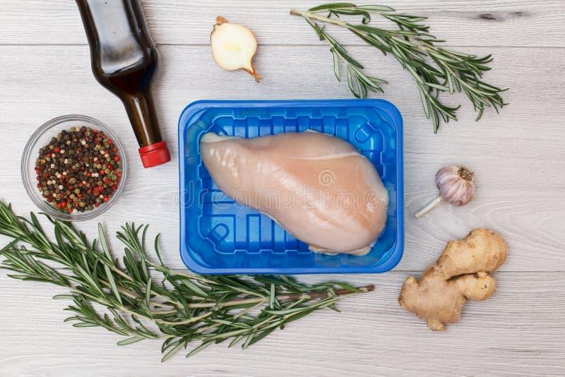 Petto di pollo o raccordo crudo in recipiente di plastica con gli ingredienti per la cottura su un fondo di legno immagine stock