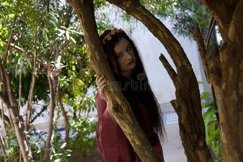 Petulant hippie girl leans against a tree stock photos