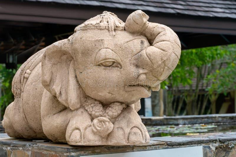 Peu éléphant drôle, sculpture, se reposant sous un parapluie mensonges image stock