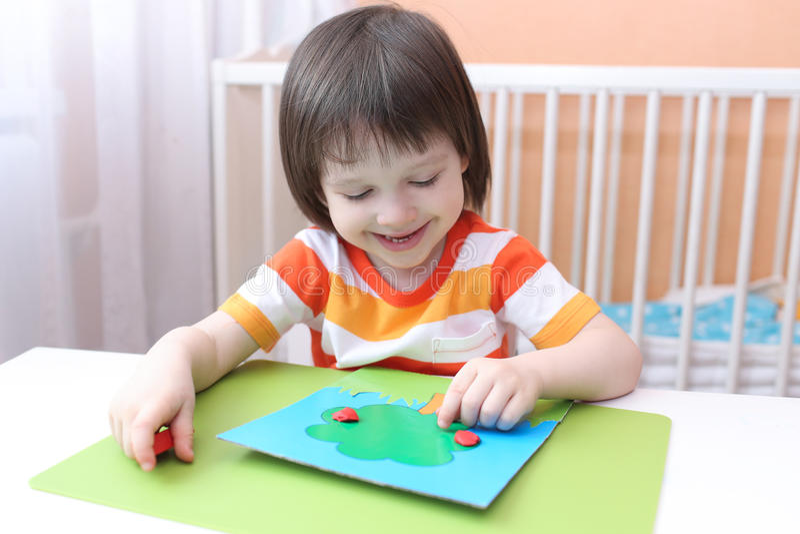 Peu 3 ans de garçon modelant le pommier du playdough images libres de droits