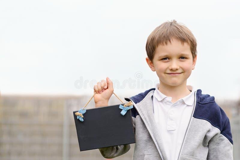 Peu 7 ans de garçon tenant un tableau noir vide images stock