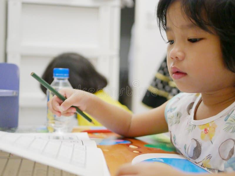 Peu bébé asiatique apprenant à écrire à la maison photos libres de droits