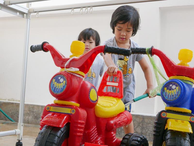 Peu bébé asiatique apprenant à laver de grands vélos en plastique tandis que sa petite soeur observant et se tenant tout près image stock
