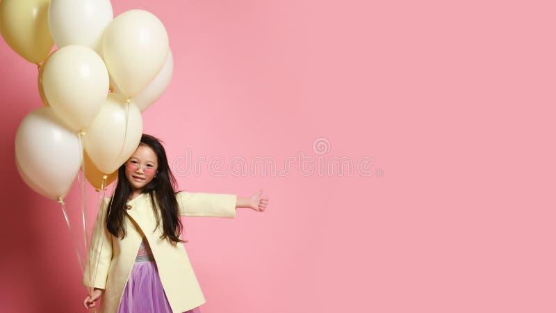 Peu bébé asiatique dans la veste jaune de mode et robe pourpre avec des ballons célèbrent le pouce de sourire heureux  photographie stock