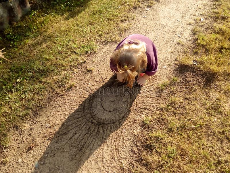 Peu bébé dessine le soleil au milieu d'une route arénacée de village images stock