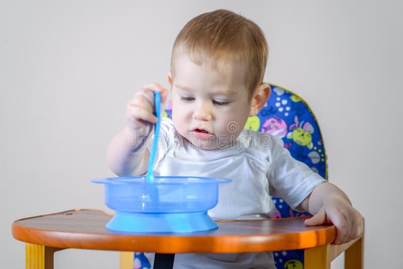 Peu bébé garçon apprenant à manger à une table étudiant un plat et une cuillère dans la cuisine images libres de droits