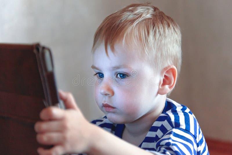 Peu bébé garçon caucasien utilise un comprimé, voyant à l'écran Dépense de temps d'enfants, automatisation des jeunes images stock