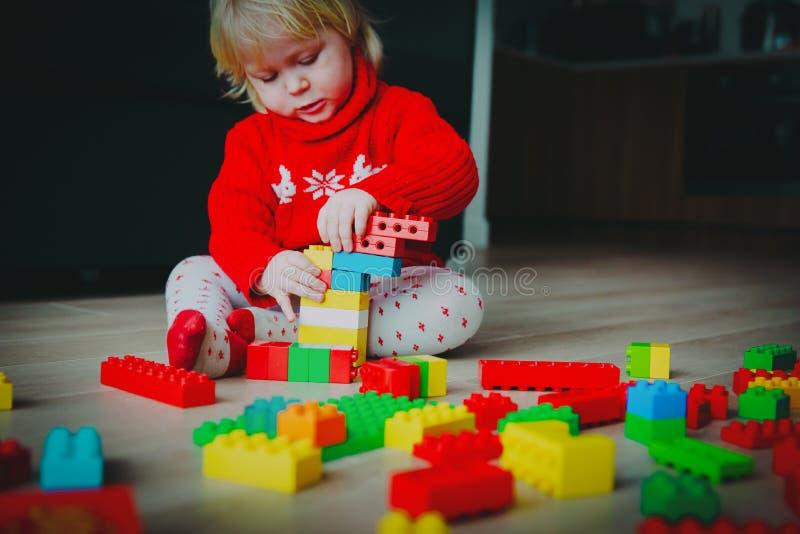 Peu bébé jouant avec les blocs en plastique colorés à la maison image libre de droits