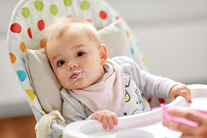 Peu bébé mangeant dans le highchair à la maison photos stock