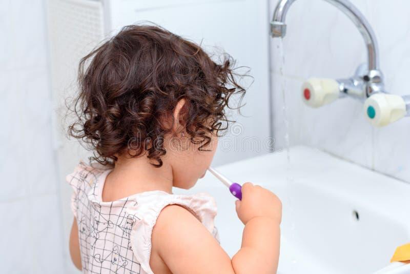 Peu bébé mignon nettoyant ses dents avec la brosse à dents dans la salle de bains photo stock
