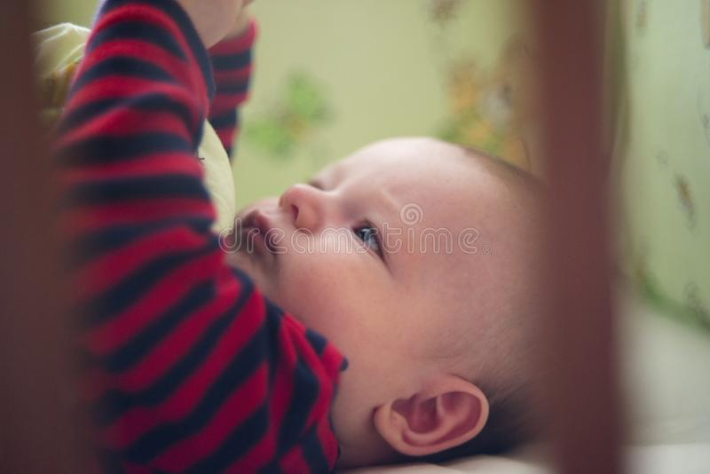 Peu bébé mignon se situant dans le lit avec la literie verte photo libre de droits