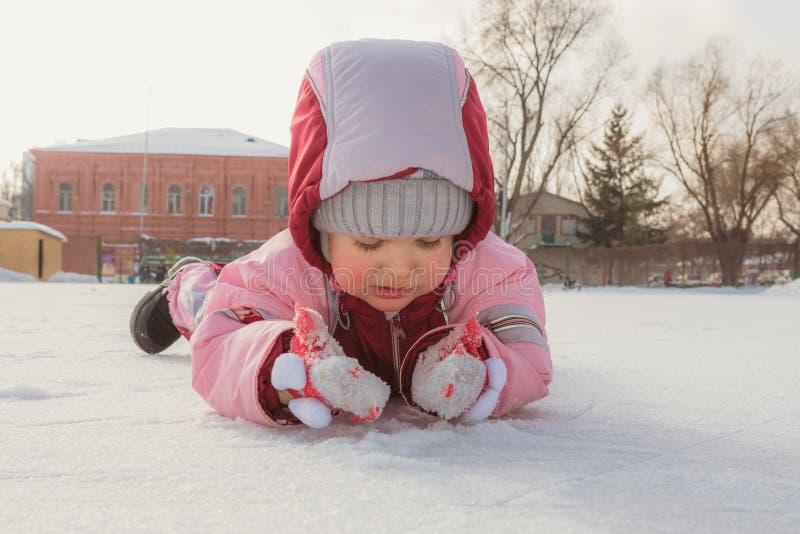 Peu bébé se trouve sur la glace en hiver photos stock