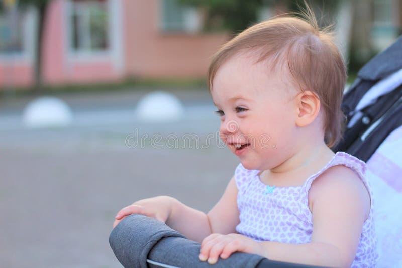 peu, beau, souriant, bébé roux mignon dans des -de-portes d'un landau dans une chemise sans manche photographie stock libre de droits