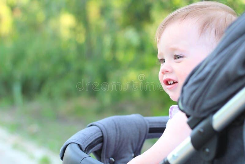 peu, beau, souriant, bébé roux mignon dans des -de-portes d'un landau dans une chemise sans manche photo stock
