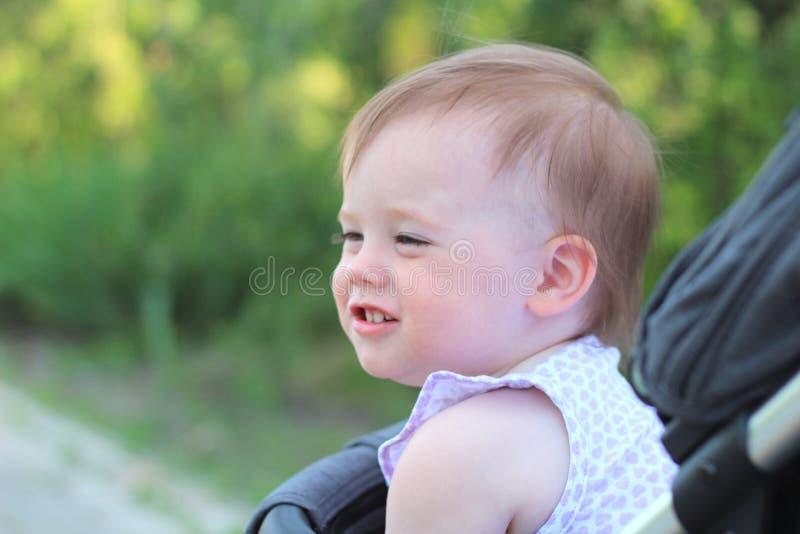 peu, beau, souriant, bébé roux mignon dans des -de-portes d'un landau dans une chemise sans manche images stock