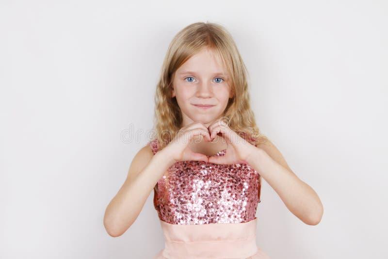 Peu belle fille blonde faisant la forme de coeur avec des mains images stock