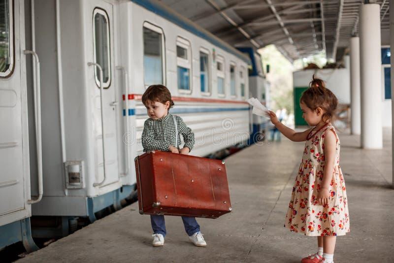 Peu belle fille dans la rétro robe indique au revoir à la station avec un petit garçon dans des vêtements de cru avec la rétro va photographie stock libre de droits