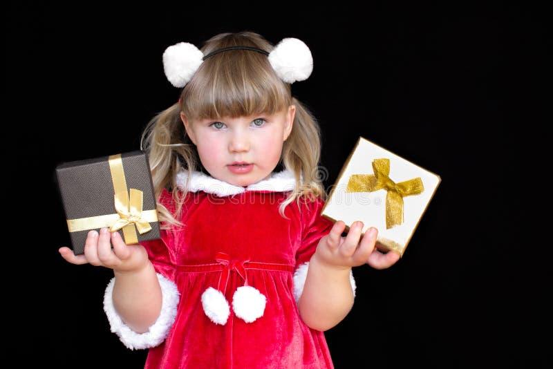 Peu belle fille dans un costume de Santa de Noël, avec des boules de fourrure sur sa tête, tient des cadeaux dans des ses mains e photos libres de droits