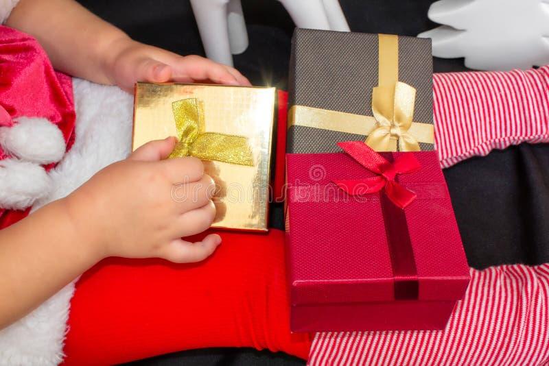 Peu belle fille dans un costume de Santa de Noël, avec des boules de fourrure sur sa tête, tient des cadeaux dans des ses mains e photo libre de droits