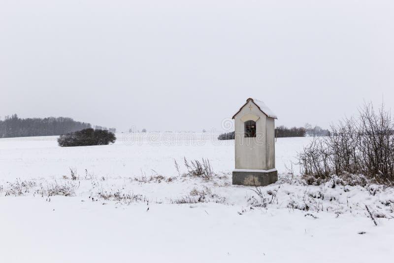 Peu chapelle dans le domaine couvert par neige Campagne tchèque image stock