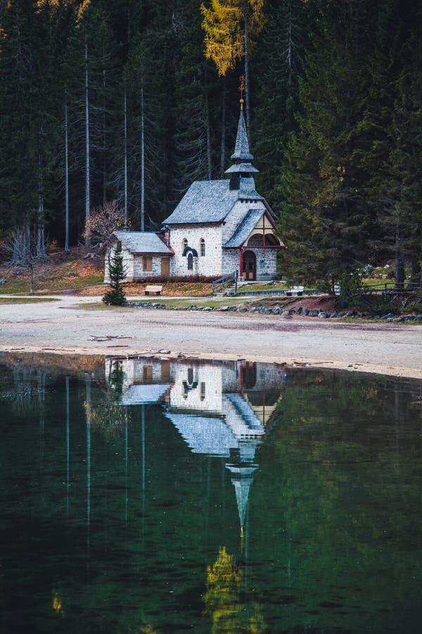 Peu chapelle se reflétant en Lago di Braies dans la chute, dolomites, Tyrol du sud, Italie photo stock