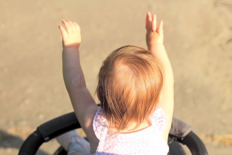 peu, dépréciez, beau, en souriant, le bébé roux mignon dans une chemise sans manche dans des -de-portes d'un landau soulève ses m photo libre de droits