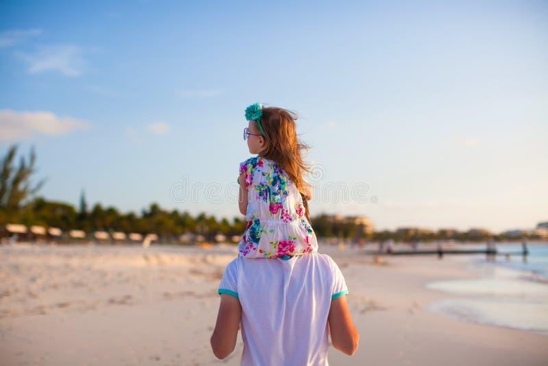 Peu d'équitation de fille de еу de ³ du  Ð de Ñ sur son papa marchant par la plage photographie stock
