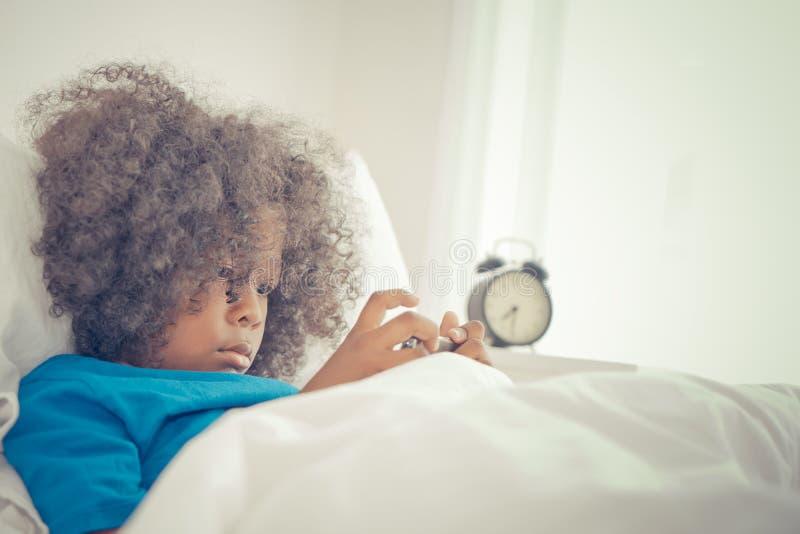 Peu d'enfant à l'aide du téléphone portable pour observer la vidéo de bande dessinée dans le lit de matin photo stock
