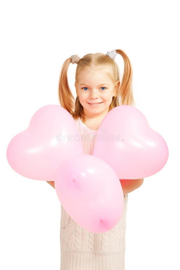 Peu d'enfant avec des ballons sous forme de coeur. photo stock
