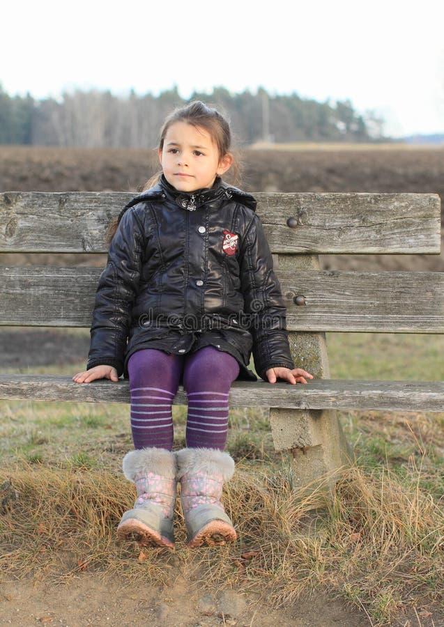 Peu d'enfant - fille s'asseyant sur un banc image stock