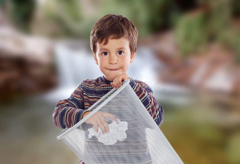 Peu d'enfant jetant un papier dans la poubelle photo stock