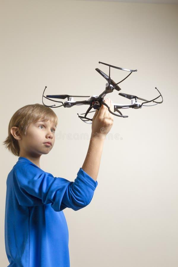 Peu d'enfant jouant avec le bourdon Garçon tenant le quadcopter dans sa main, préparant pour voler image stock