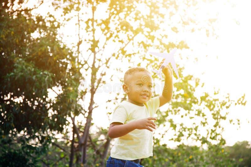 Peu d'enfant jouant avec le jouet d'avion en parc vert image stock